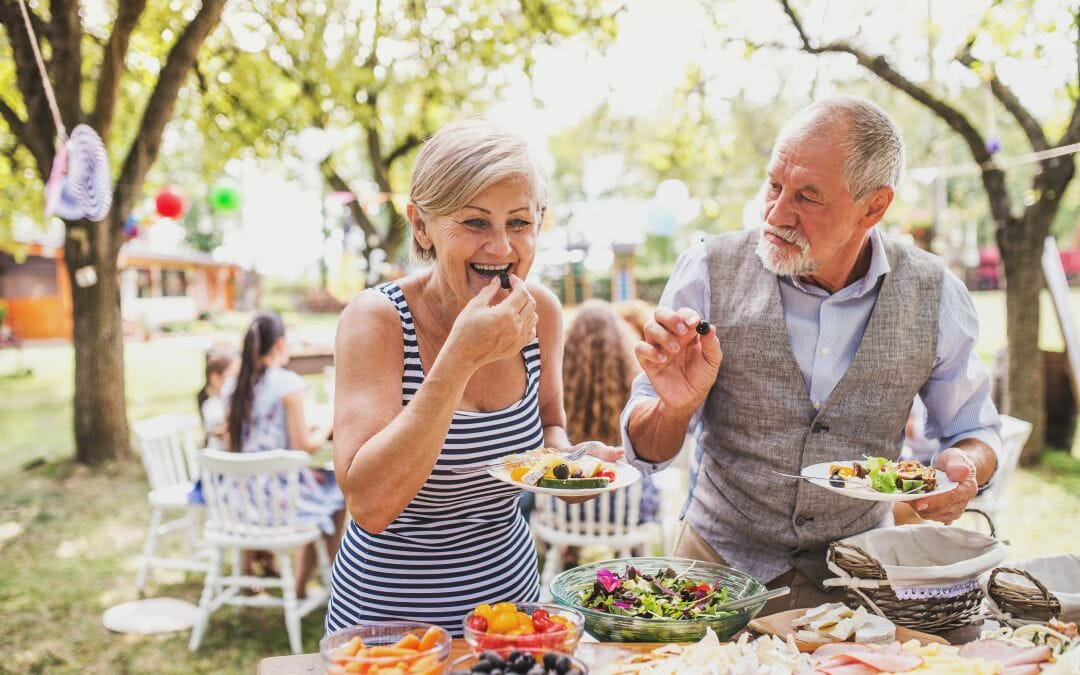 older couple eating food at an outdoor picnic