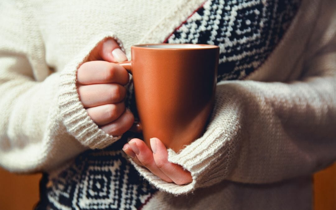 woman in sweater holding cup of coffee
